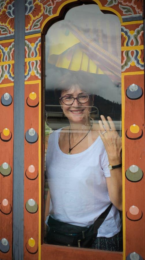 Piękna Kaukaska kobieta ono uśmiecha się za brudnym okno restauracja w Punakha, Bhutan obraz royalty free