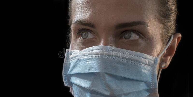 Piękna, kaukaska zarażona dziewczyna na czarnym tle w masce medycznej z napisem 2019-nCov Koncepcja Coronavirus covid-19 zdjęcie royalty free
