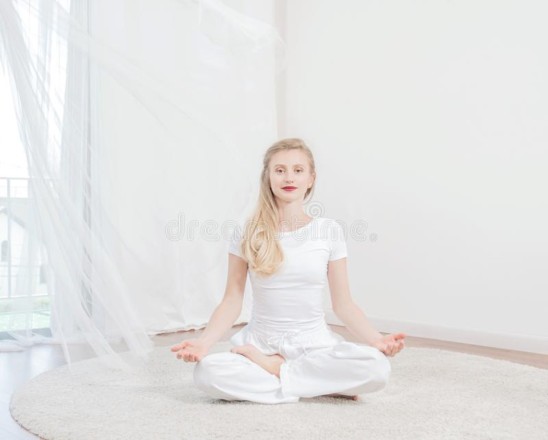 Piękna kobieta ćwiczy joga w domu, dziewczyna robi Padmasana ćwiczeniu, siedzi w Lotosowej pozie obrazy stock