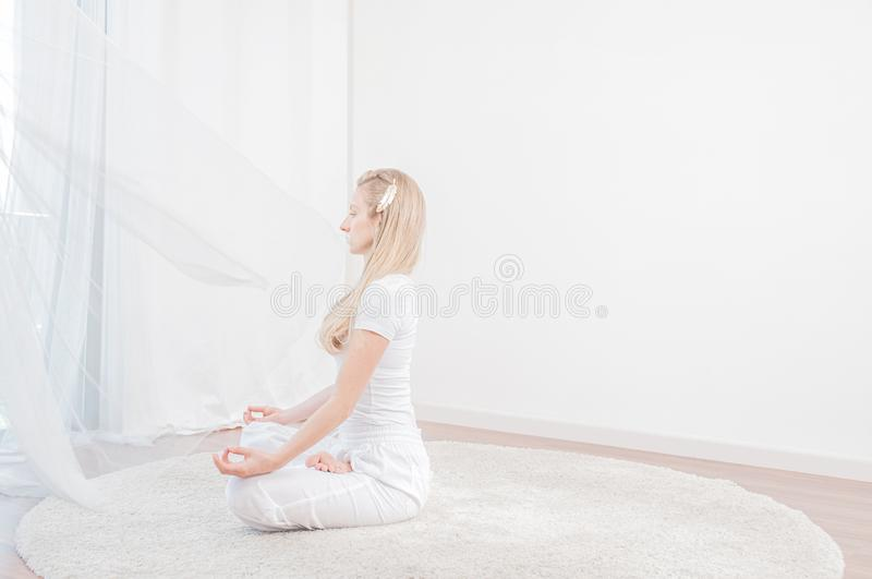 Piękna kobieta ćwiczy joga w domu, dziewczyna robi Padmasana ćwiczeniu, siedzi w Lotosowej pozie obraz royalty free