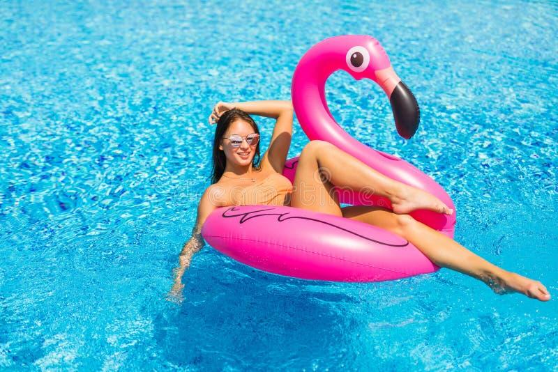 Piękna kobieta, będący ubranym swimsuit, kłama na różowego flaminga lotniczej materac w basenie błękitne wody, lato zdjęcia stock