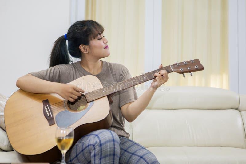 Piękna kobieta bawić się gitarę akustyczną w domu obraz royalty free
