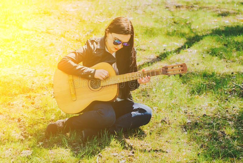 Piękna kobieta bawić się gitary akustycznej czerń zdjęcie stock
