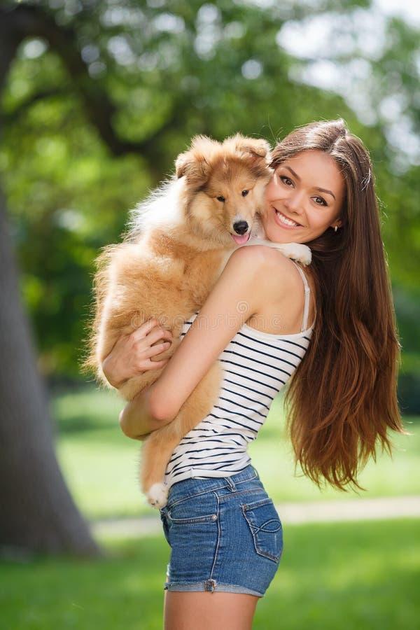Piękna kobieta bawić się w parku z szczeniaka collie fotografia royalty free