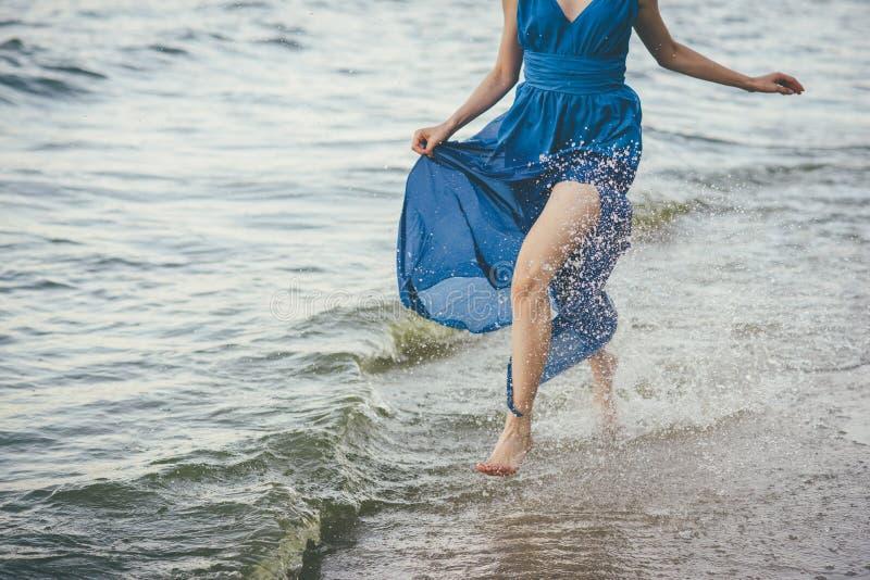 Piękna kobieta biegająca wzdłuż brzegu wody fotografia royalty free
