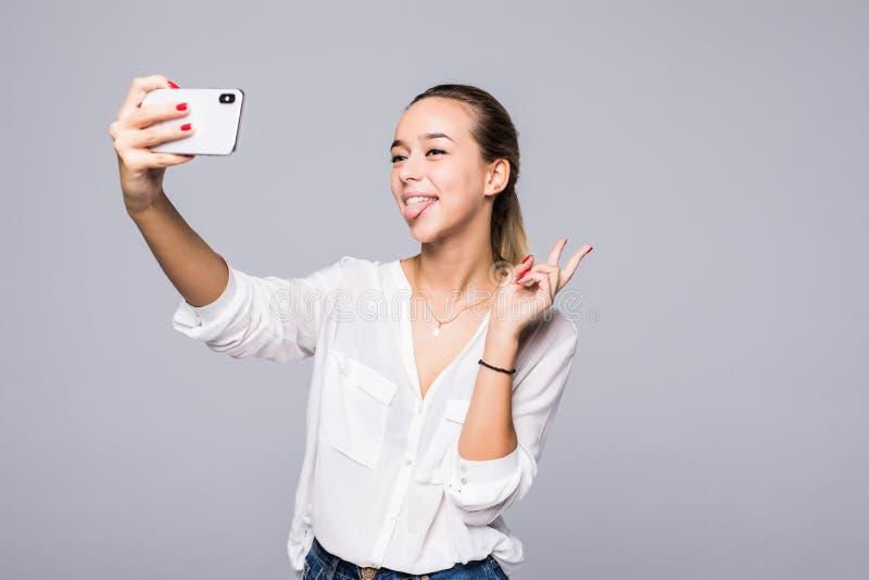 Piękna kobieta bierze selfie i pokazuje zwycięstwo znaka z doskonalić uśmiechem odizolowywającym nad szarym tłem obraz royalty free