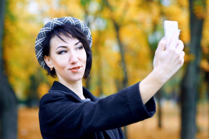 Piękna kobieta bierze selfie smartphone i ma zabawę w jesieni miasta parku, sezon jesienny, kolor żółty opuszcza zdjęcia royalty free