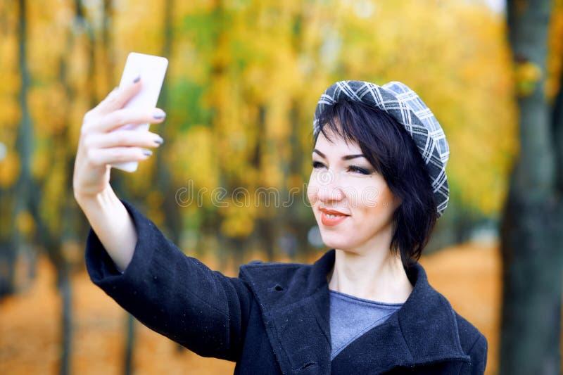 Piękna kobieta bierze selfie smartphone i ma zabawę w jesieni miasta parku, sezon jesienny, kolor żółty opuszcza zdjęcie stock