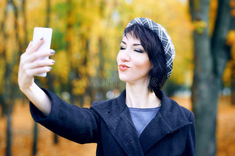 Piękna kobieta bierze selfie smartphone i ma zabawę w jesieni miasta parku, sezon jesienny, kolor żółty opuszcza zdjęcia stock