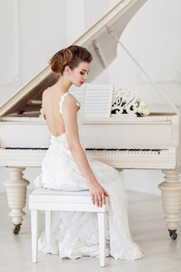 Piękna kobieta blisko białego pianina zdjęcia royalty free