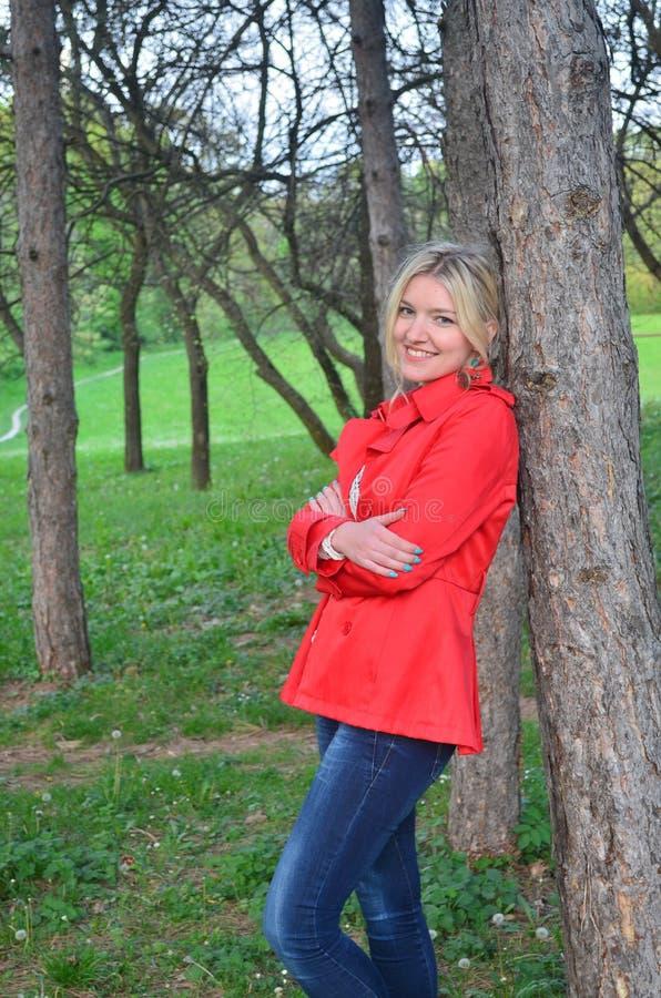 Piękna kobieta blisko drzewa w czerwonej kurtce fotografia royalty free