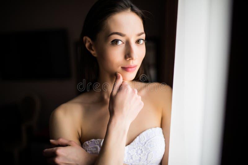 Piękna kobieta blisko zasłoien nadokienny i patrzeć kamerę zdjęcia stock