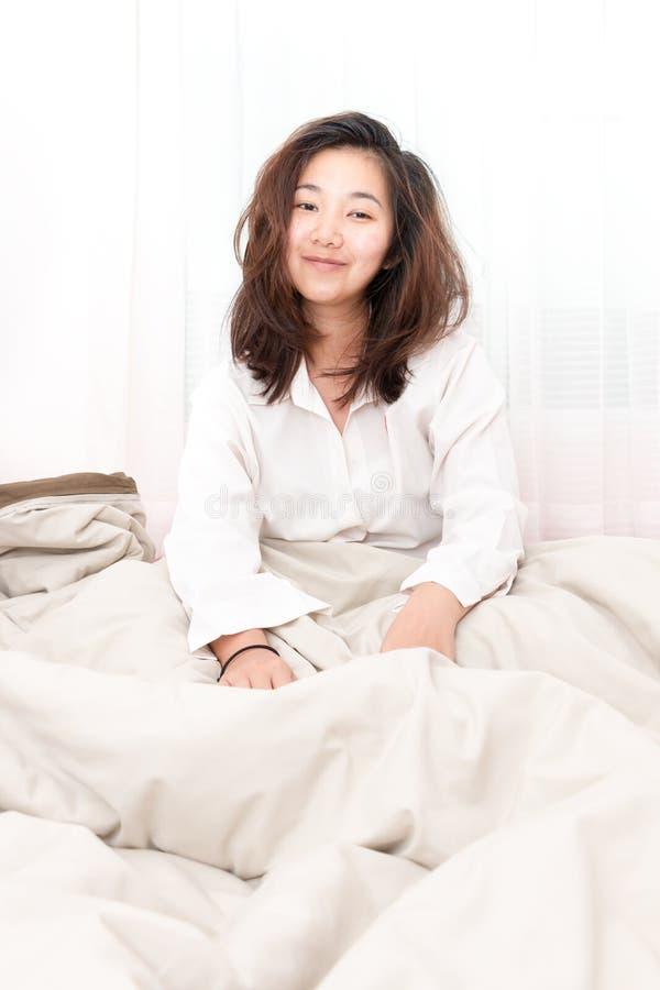 Piękna kobieta budzi się up w jej łóżku w sypialni obraz stock
