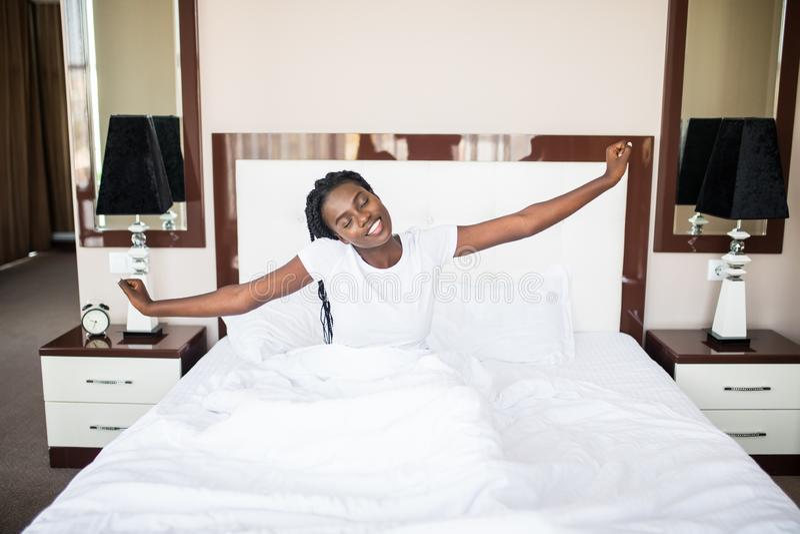 Piękna kobieta budzi się w jej łóżku, jest uśmiechnięta i rozciągająca w domu obraz royalty free