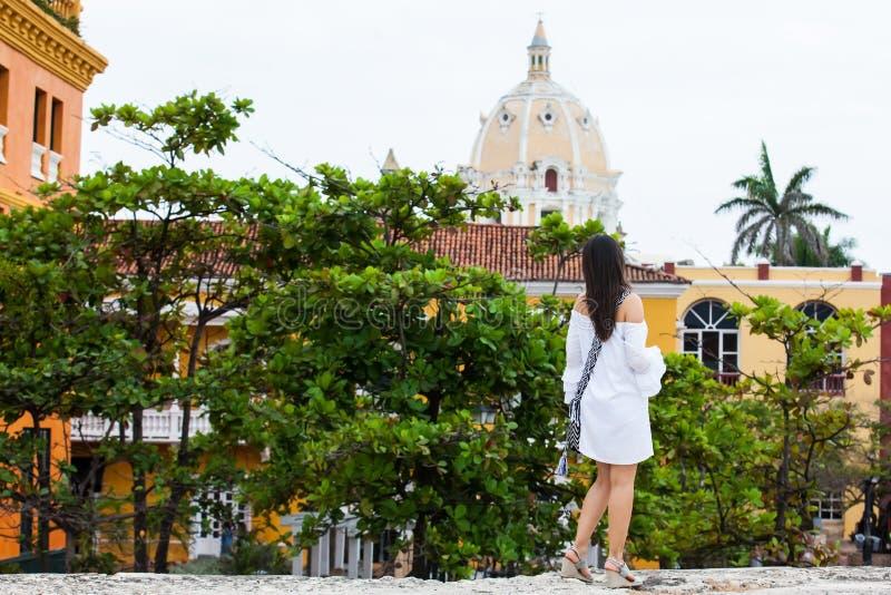 Piękna kobieta chodzi samotnie przy ścianami otacza kolonialnego miasto Cartagena De Indias na biel sukni obraz stock