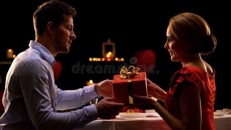 Piękna kobieta daje czerwonemu prezenta pudełku zdziwiony ukochany mężczyzna, był mój valentine fotografia royalty free