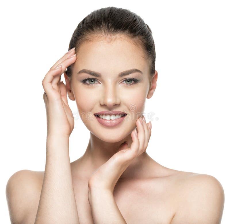 Piękna kobieta dba dla skóry twarzy - odizolowywającej na bielu obrazy royalty free