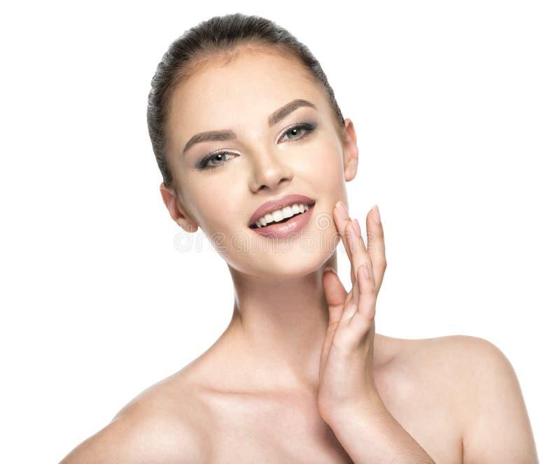 Piękna kobieta dba dla skóry twarzy - odizolowywającej na bielu zdjęcia royalty free