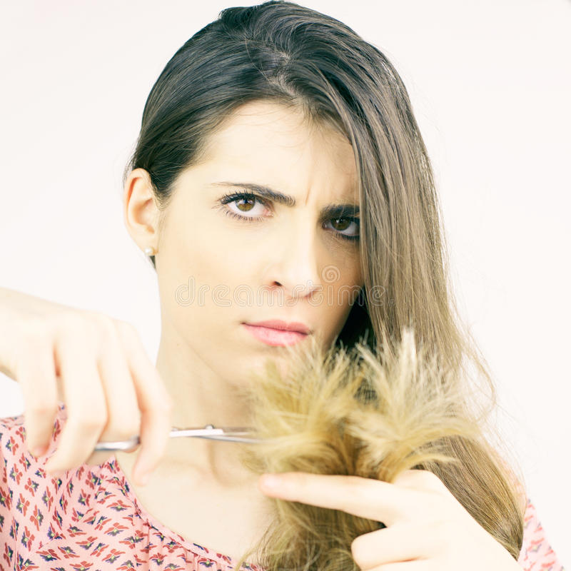 Piękna kobieta decyduje cięcie rozszczepionych końcówek włosiana przyglądająca kamera odizolowywająca zdjęcie stock