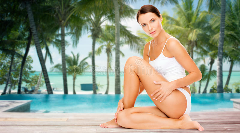 Piękna kobieta dotyka jej biodra nad plażą obraz stock