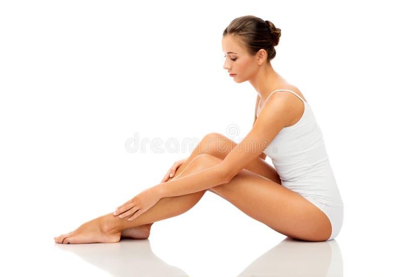 Piękna kobieta dotyka jej gładkiego ogołaca nogi obraz royalty free