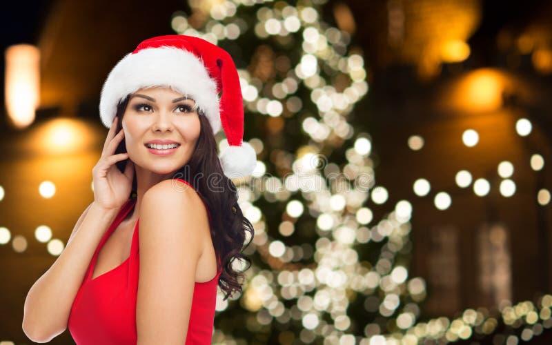 Piękna kobieta dzwoni na telefonie komórkowym przy bożymi narodzeniami zdjęcie stock