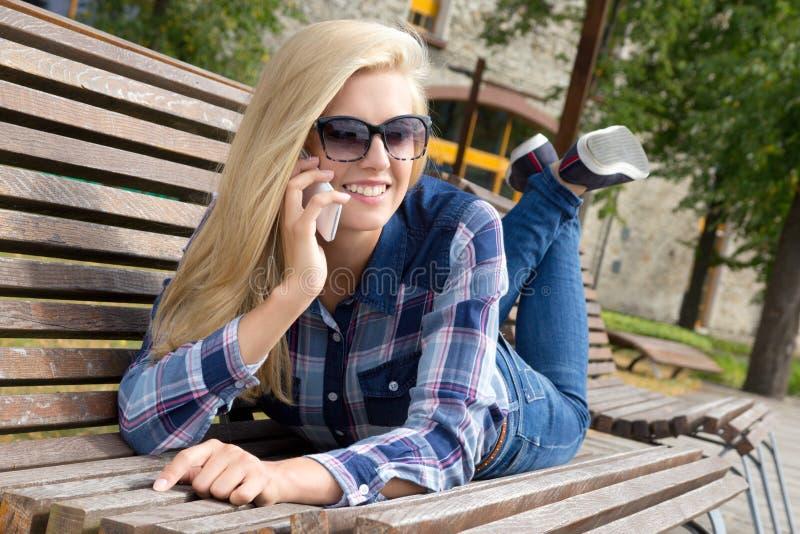 Piękna kobieta dzwoni telefonem i lying on the beach na ławce w parku fotografia stock