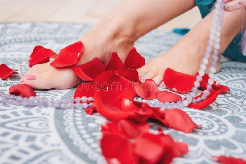 Piękna kobieta garbnikująca iść na piechotę z różowym pedicure'em wśród różanych płatków, w górę zdjęcie stock