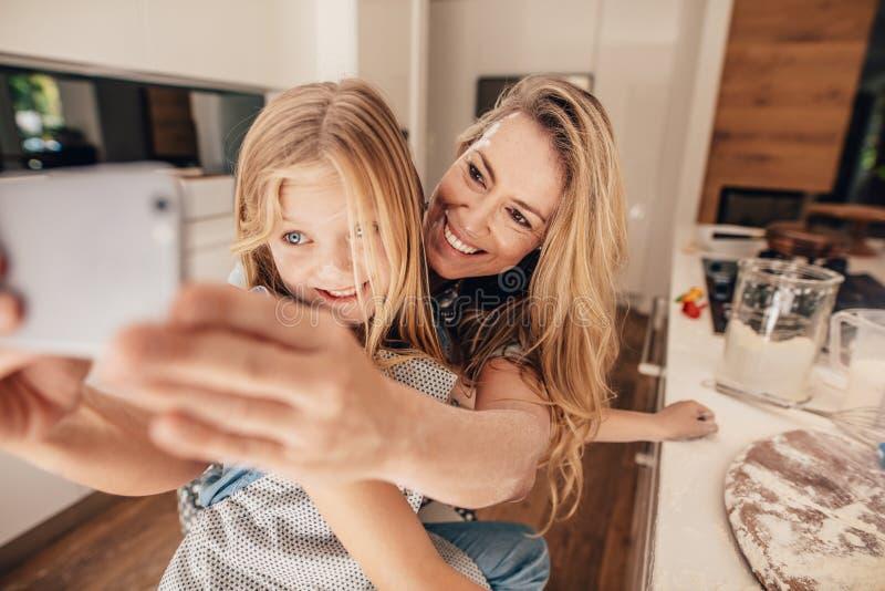 Piękna kobieta i jej śliczna córka bierze selfie w kuchni fotografia stock