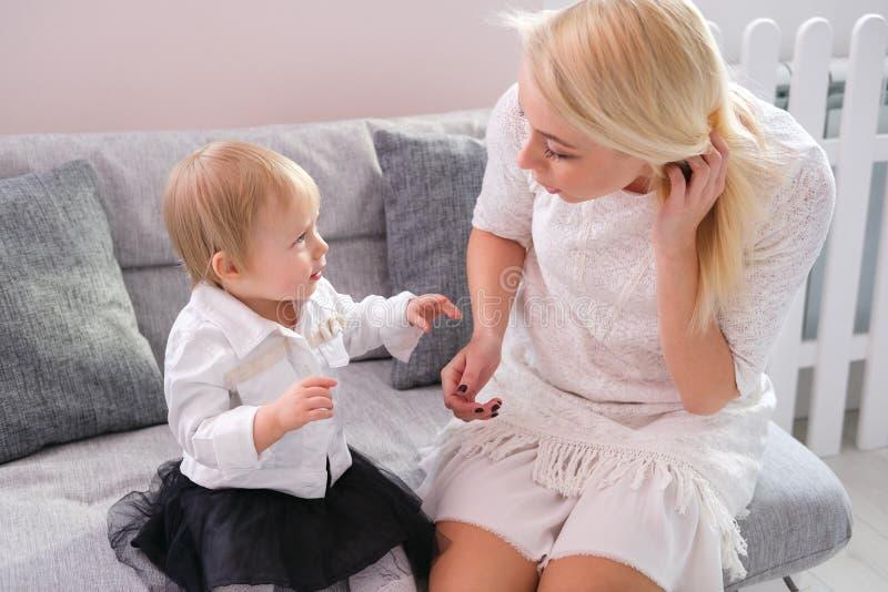 Piękna kobieta i jej dziecko bawić się siedzieć na kanapie w białym pokoju obrazy stock
