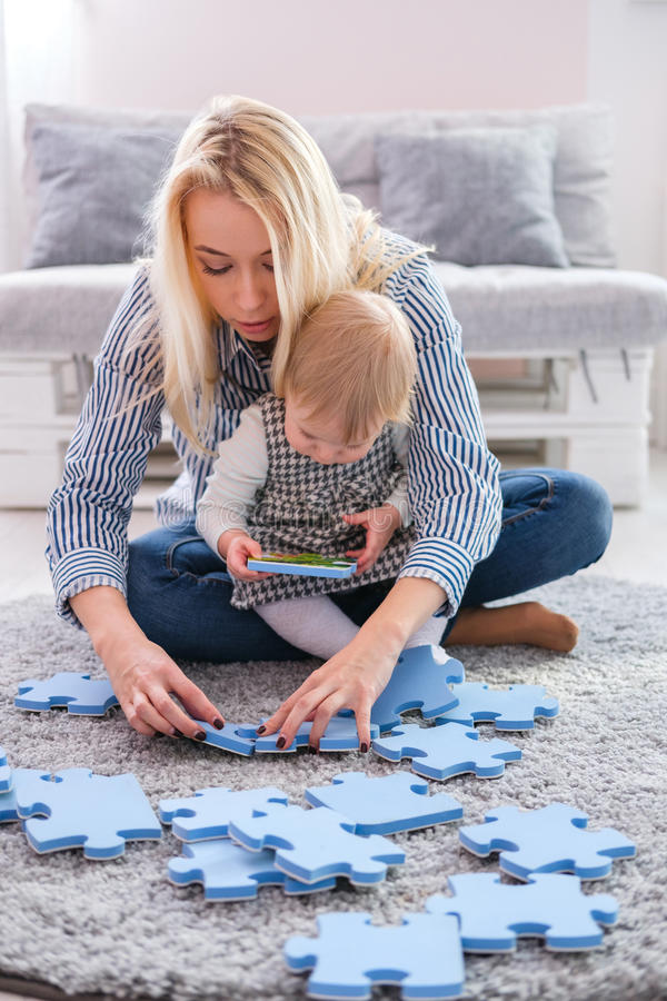 Piękna kobieta i jej dziecko bawić się z łamigłówka kawałkami podczas gdy siedzący na dywanie w żywym pokoju zdjęcia royalty free
