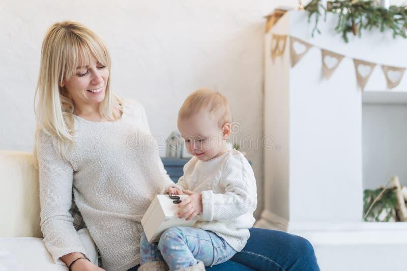 Piękna kobieta i jej dziecko bawić się z zabawkarskiego pudełka obsiadaniem na kanapie w białym pokoju zdjęcie stock
