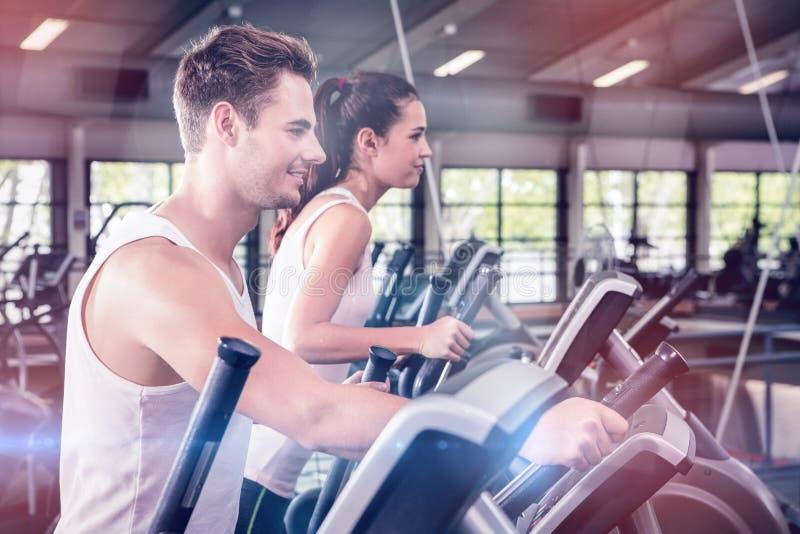Piękna kobieta i mężczyzna ćwiczy na elliptical maszynie zdjęcia stock