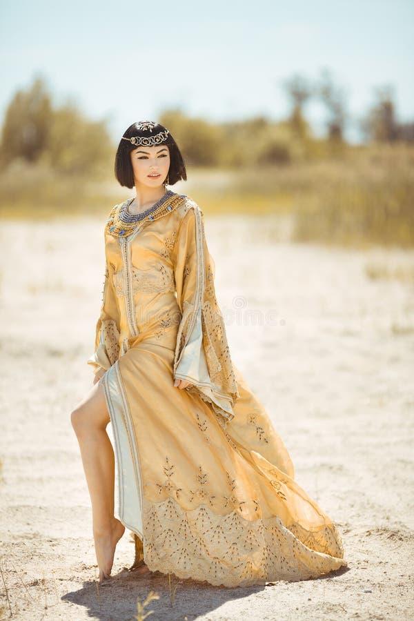 Piękna kobieta jak Egipska królowa Cleopatra dalej w pustynny plenerowym obraz stock