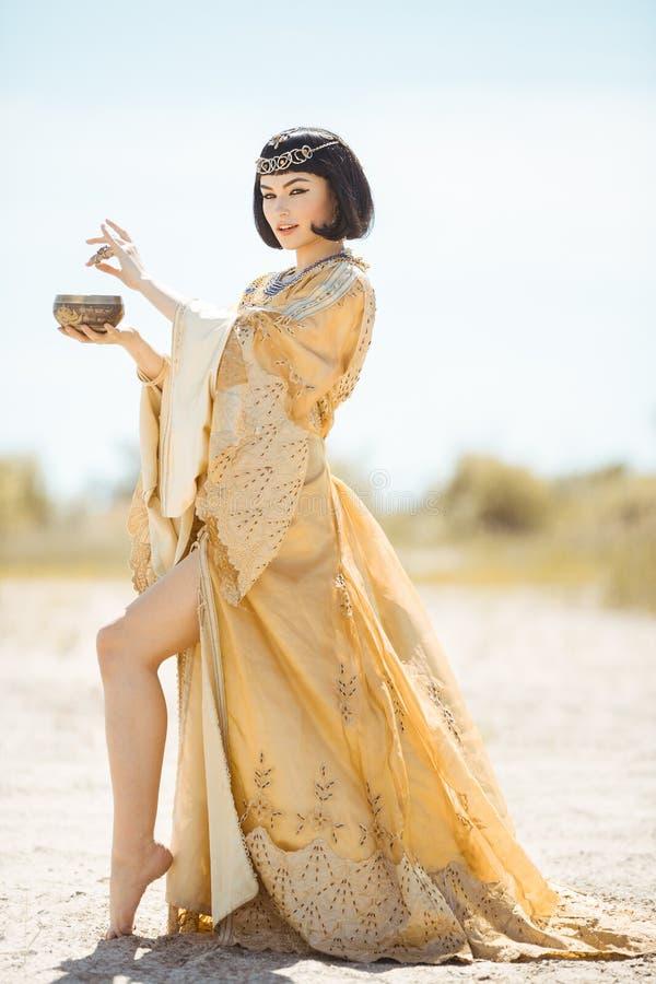 Piękna kobieta jak Egipska królowa Cleopatra z filiżanką plenerową w pustyni obraz stock