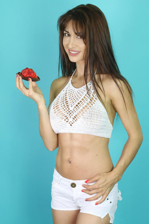 Piękna kobieta je truskawkowy tarta zdjęcia royalty free