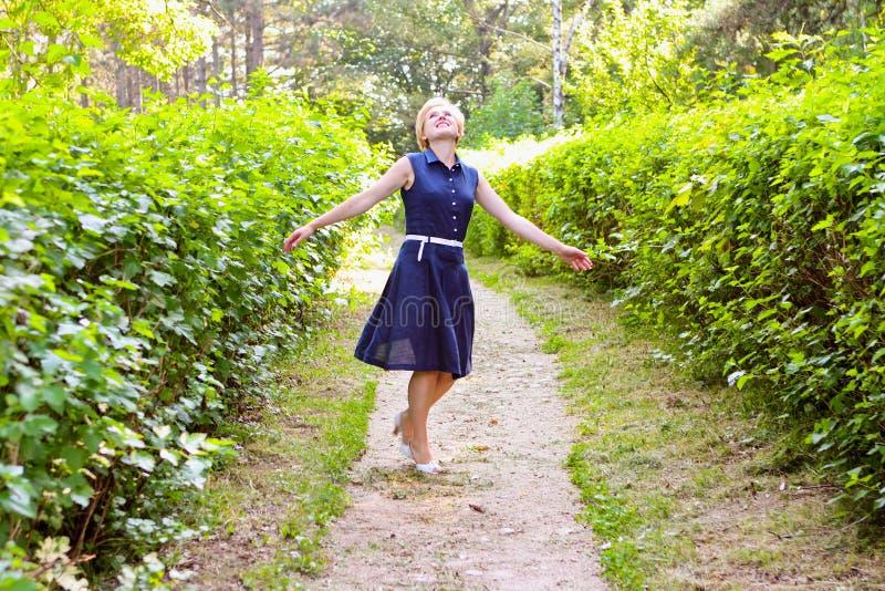 Piękna kobieta jest przędzalniana z rękami szeroko rozpościerać i ono uśmiecha się ogrodowy dzień lato obrazy royalty free
