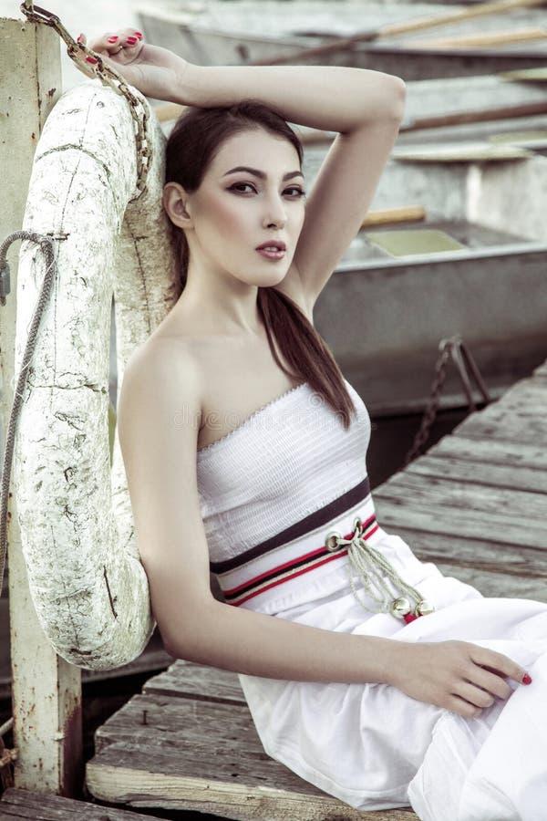 Piękna kobieta jest ubranym białego lato sukni obsiadanie na drewnianym kulebiaku zdjęcia stock