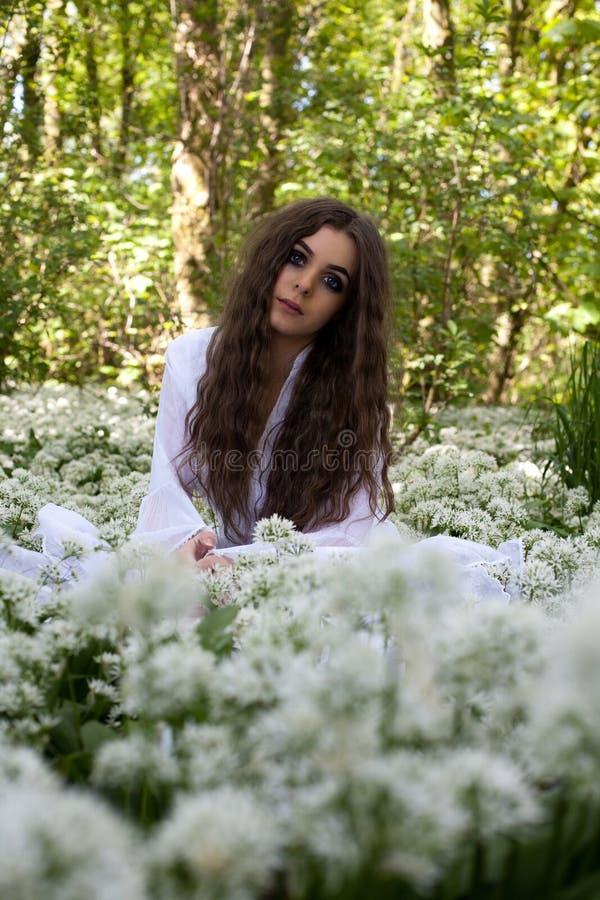 Piękna kobieta jest ubranym długiego biel sukni obsiadanie w lesie o obraz royalty free