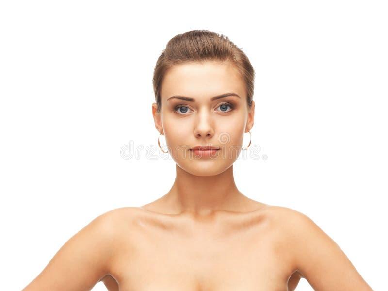 Piękna kobieta jest ubranym złocistych kolczyki zdjęcie royalty free