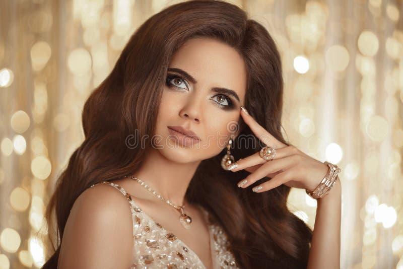 Piękna kobieta jest ubranym złotą biżuterię z perfect makeup mani obrazy royalty free