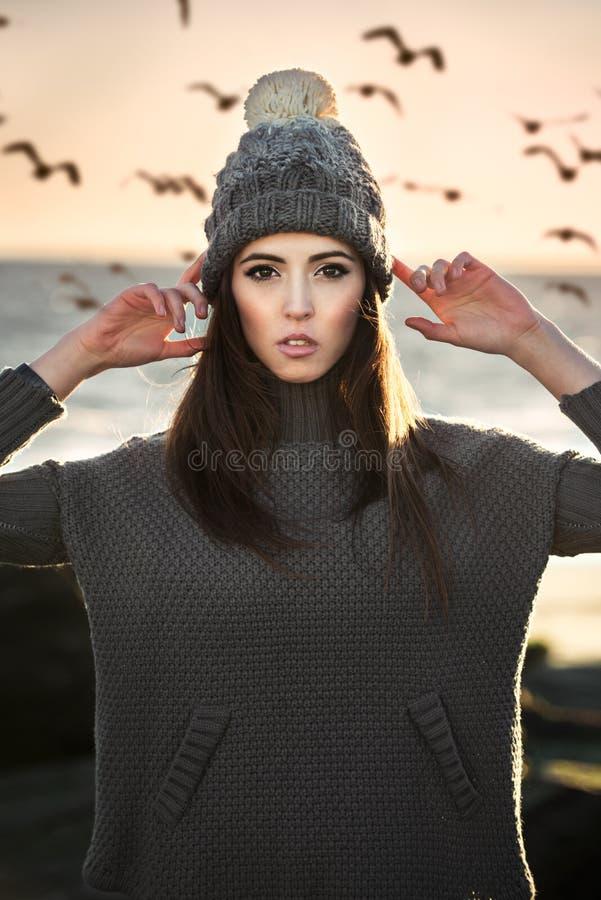 Piękna kobieta jest ubranym zimy odzieżową pozycję na plaży zdjęcia stock