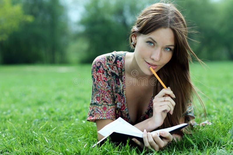 Piękna kobieta kłaść na trawie w parku z dzienniczkiem w brzęczeniach obraz stock