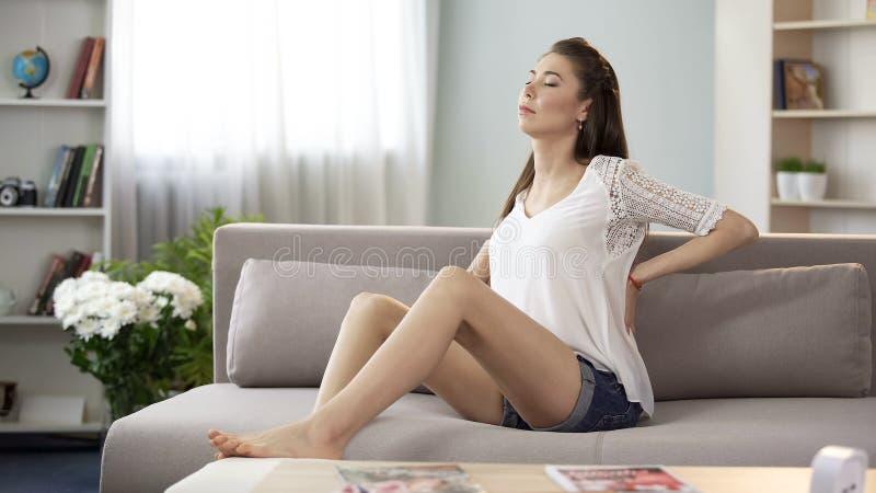 Piękna kobieta ma ból pleców, cierpi problemy zdrowotnych od sedentarnego życia zdjęcia royalty free