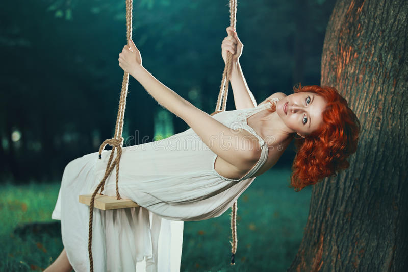 Piękna kobieta na huśtawce w lesie fotografia stock