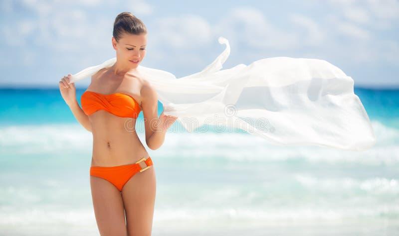 Piękna kobieta na plaży w pomarańczowym bikini fotografia stock