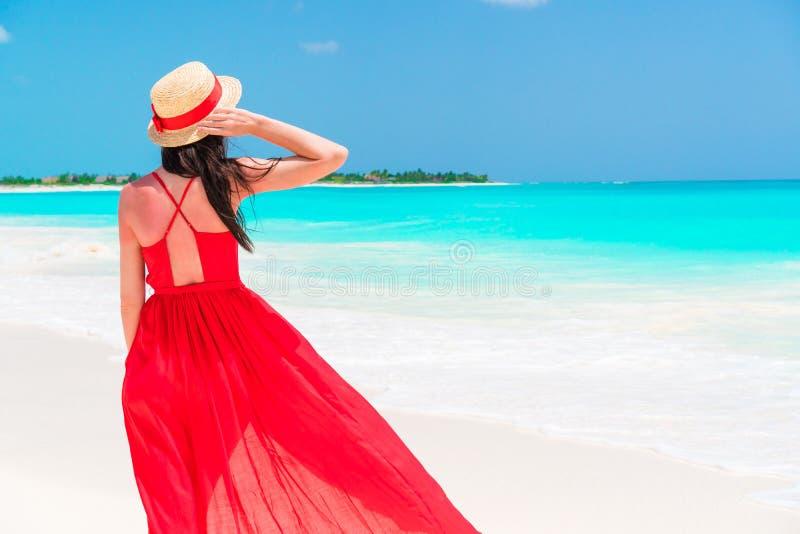 Piękna kobieta na tropikalnym seashore Młoda dziewczyna w pięknym czerwieni sukni tle morze zdjęcia royalty free