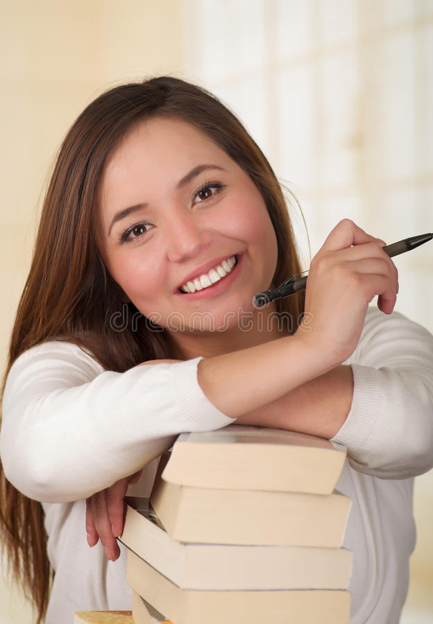 Piękna kobieta odpoczywa nad stosem książki i szczęśliwa zdjęcie stock