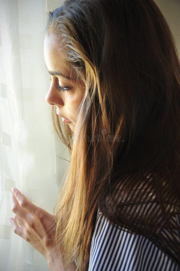 Piękna kobieta ogląda okno zdjęcie stock