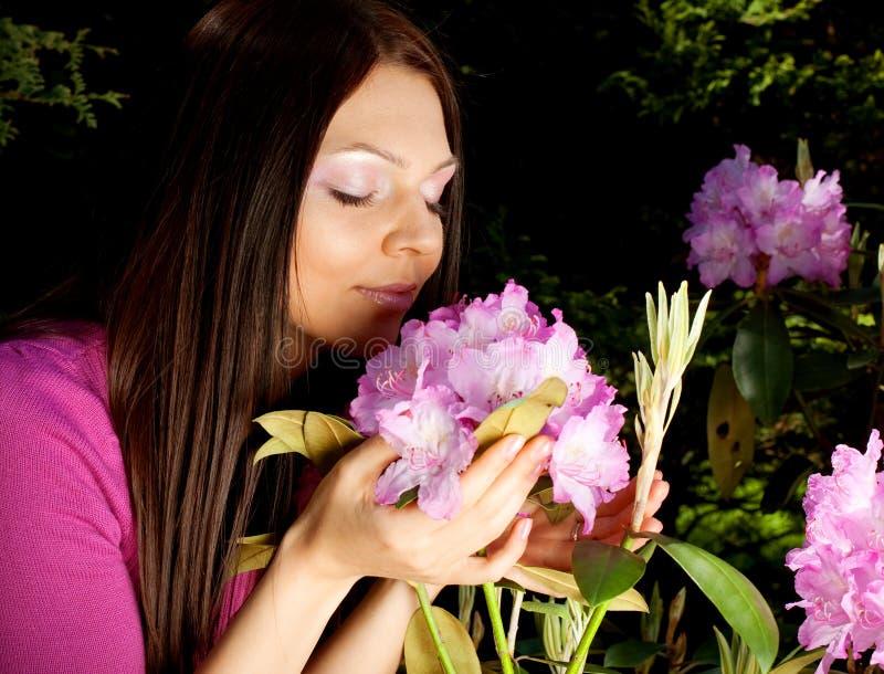 Piękna kobieta ono uśmiecha się outdoors z niektóre kwiatami zamyka w górę zdjęcia stock